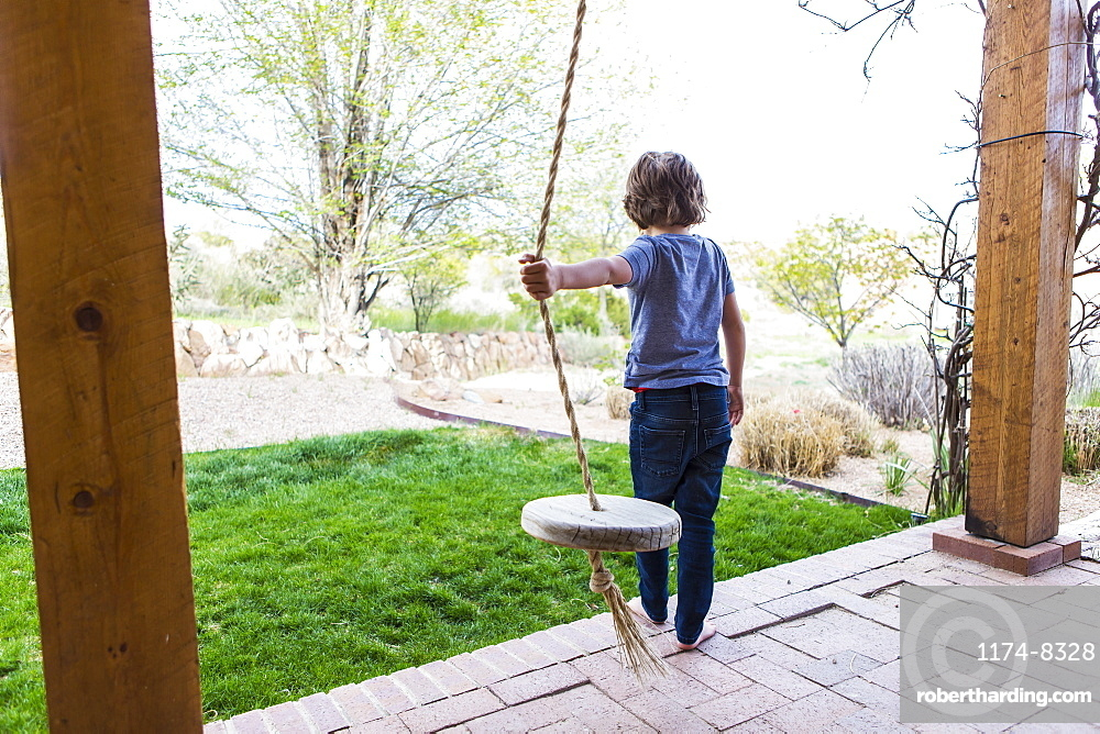 Six year old boy using a rope swing on a wide porch in the shade