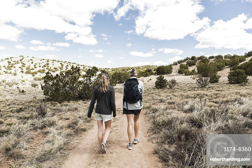 Rear view of adult woman and her teenage daughter hiking in the Galisteo Basin, New Mexico, United States of America