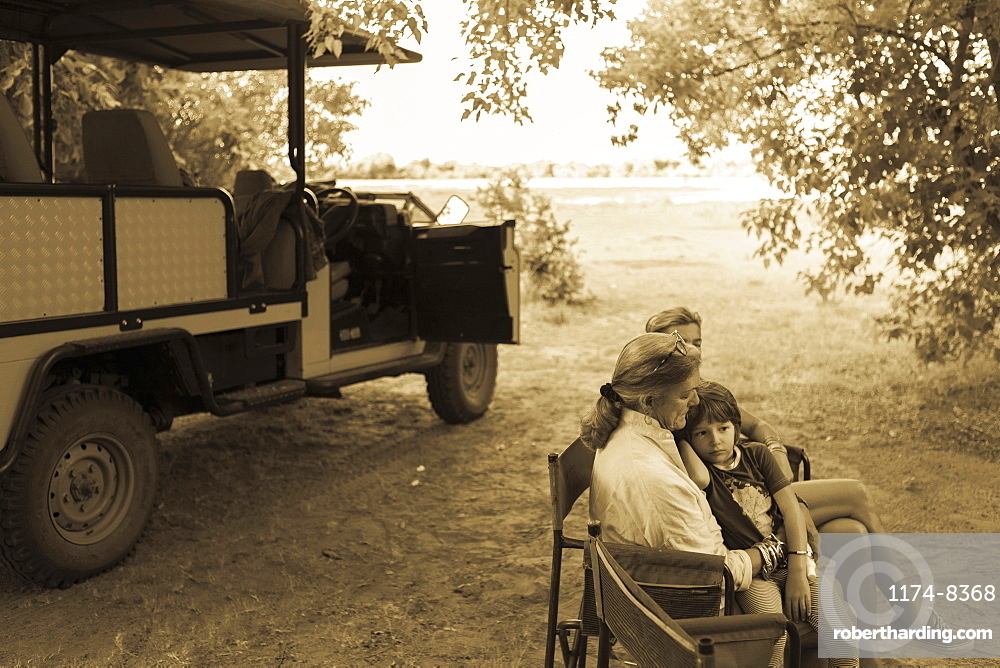 Three generations of a family seated in folding chairs by a safari jeep, under trees, monochrome, Moremi Game Reserve, Botswana