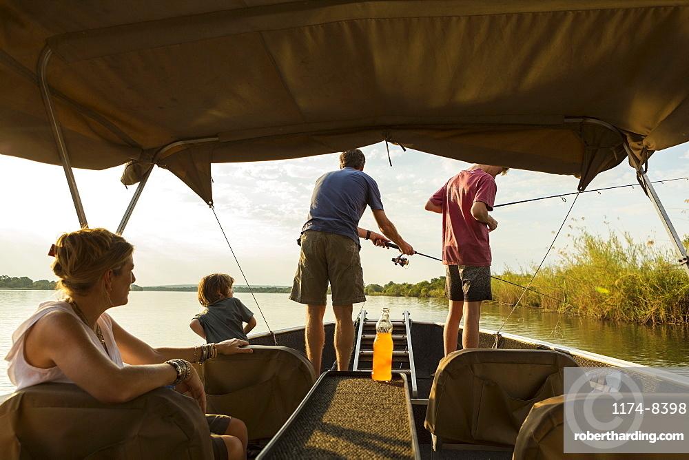 A group of tourists, family fishing from a boat on the Zambezi River, Botswana, Zambezi River, Botswana