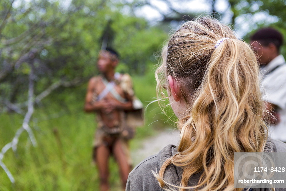 Rear view of teen girl walking with a group of bushmen from the San people