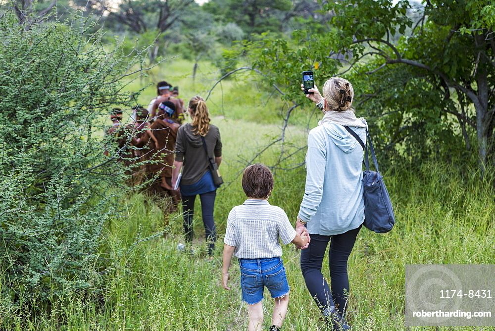 A boy and his mother, tourists on a walking trail following members of the San people, bushmen