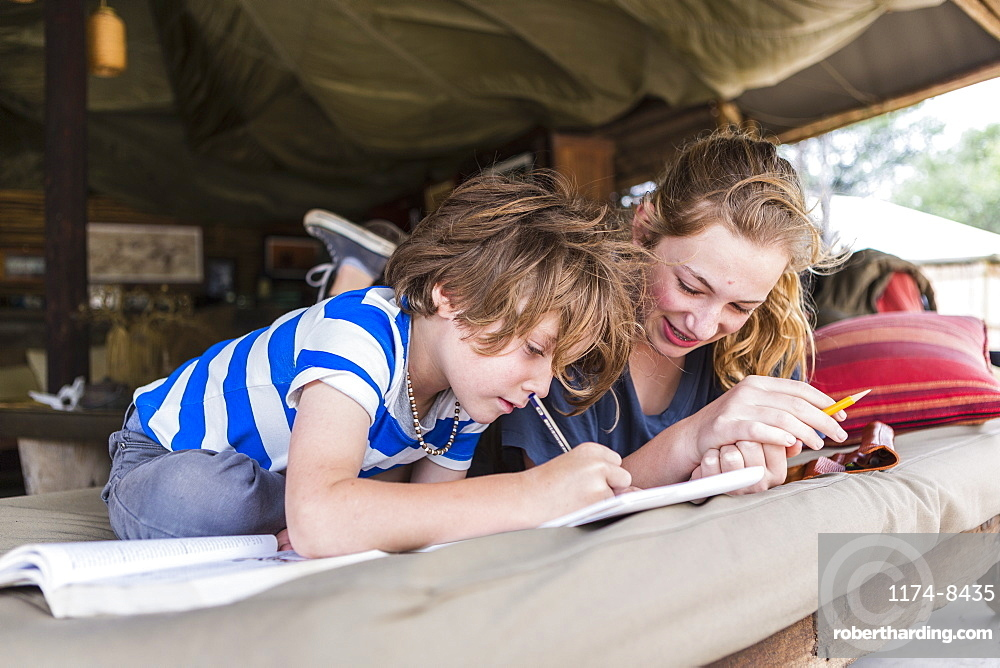 Brother and sister doing homework together in a tented camp in Botswana