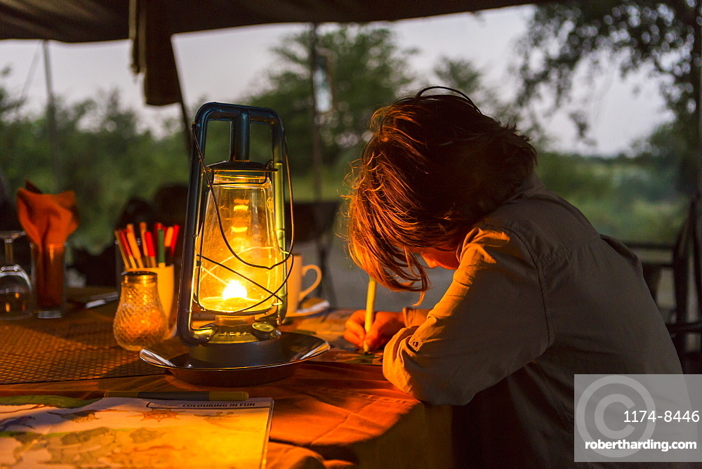 Six year old boy writing a journal by lantern light in a tented camp