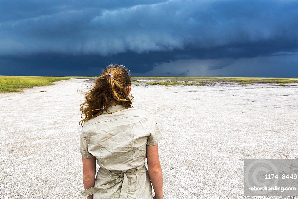 rear view of Thirteen year old girl looking at dramatic sky, Nxai Pan, Botswana