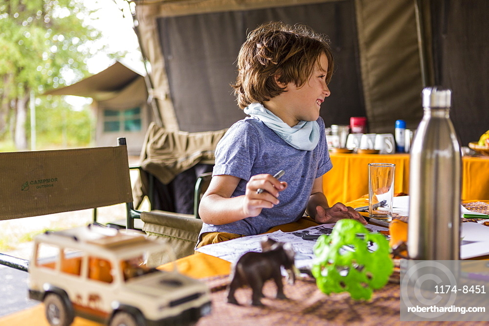 Smiling boy, profile, in a tented camp, on safari, playing with safari animal toys