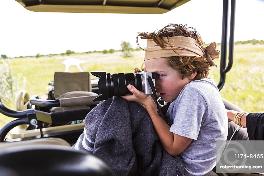 Six year old boy taking pictures from safari vehicle, Botswana