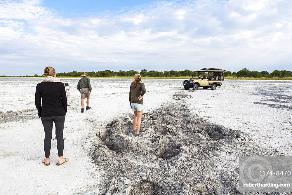 family looking at elephant footprints, Nxai Pan, Botswana