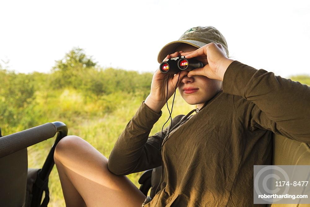 Thirteen year old girl with binoculars on safari vehicle, Botswana