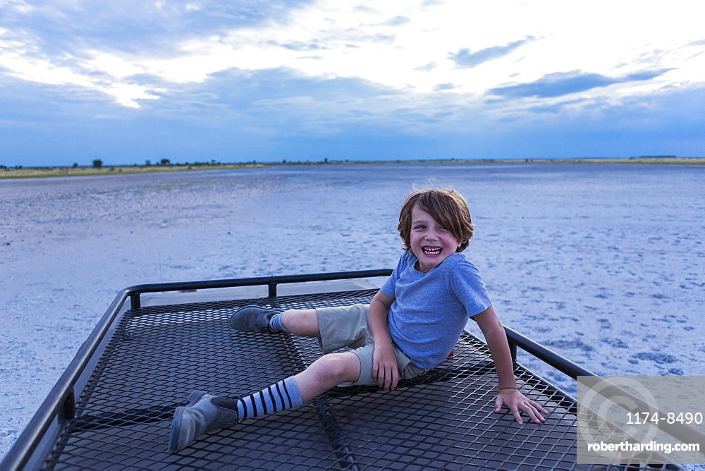 Six year old boy and guide on top of safari vehicle, Nxai Pan, Botswana