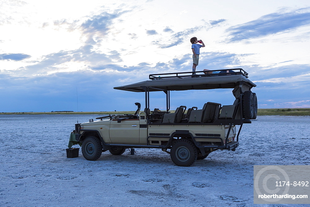 Six year old boy and older sister standing on top of safari vehicle, Nxai Pan, Botswana