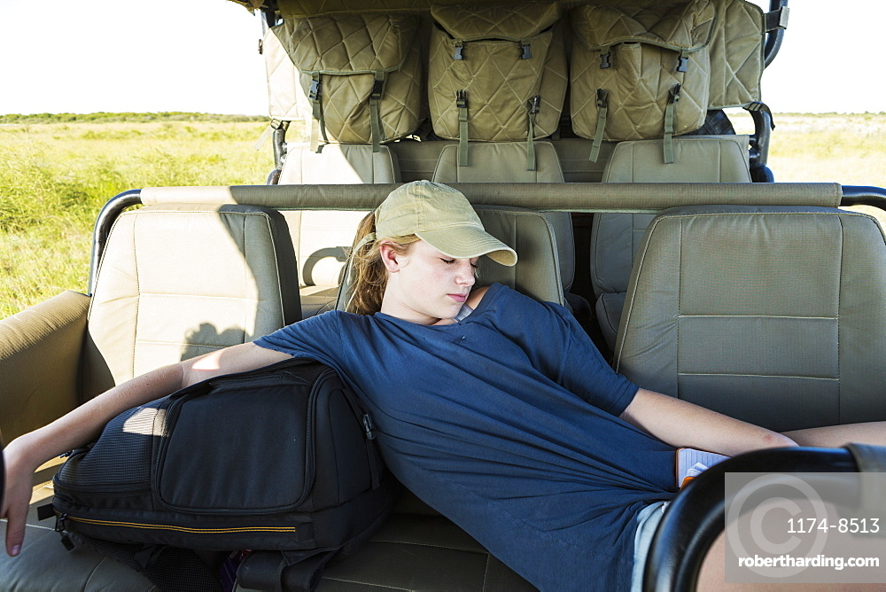 A teenage girl resting in a safari vehicle