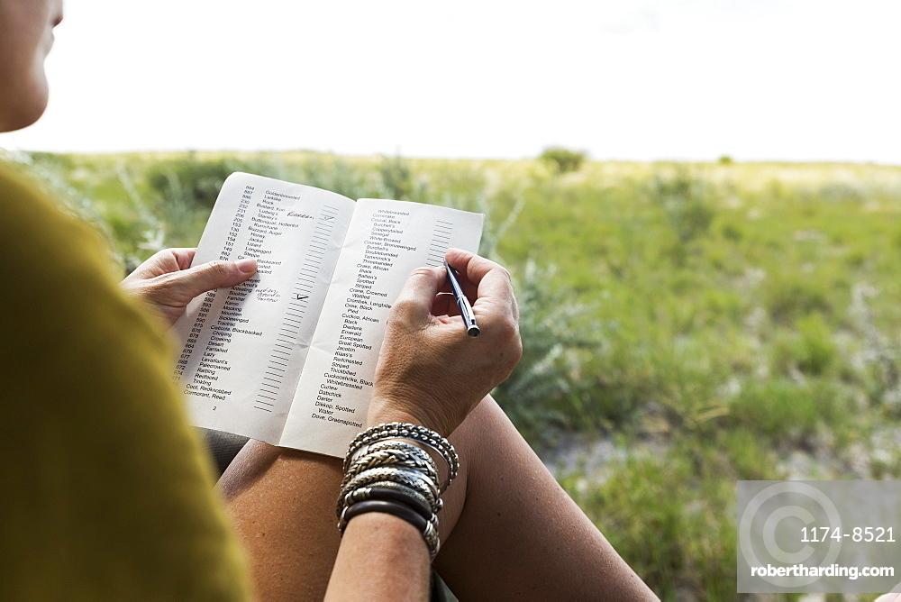 woman writing in safari vehicle, Botswana