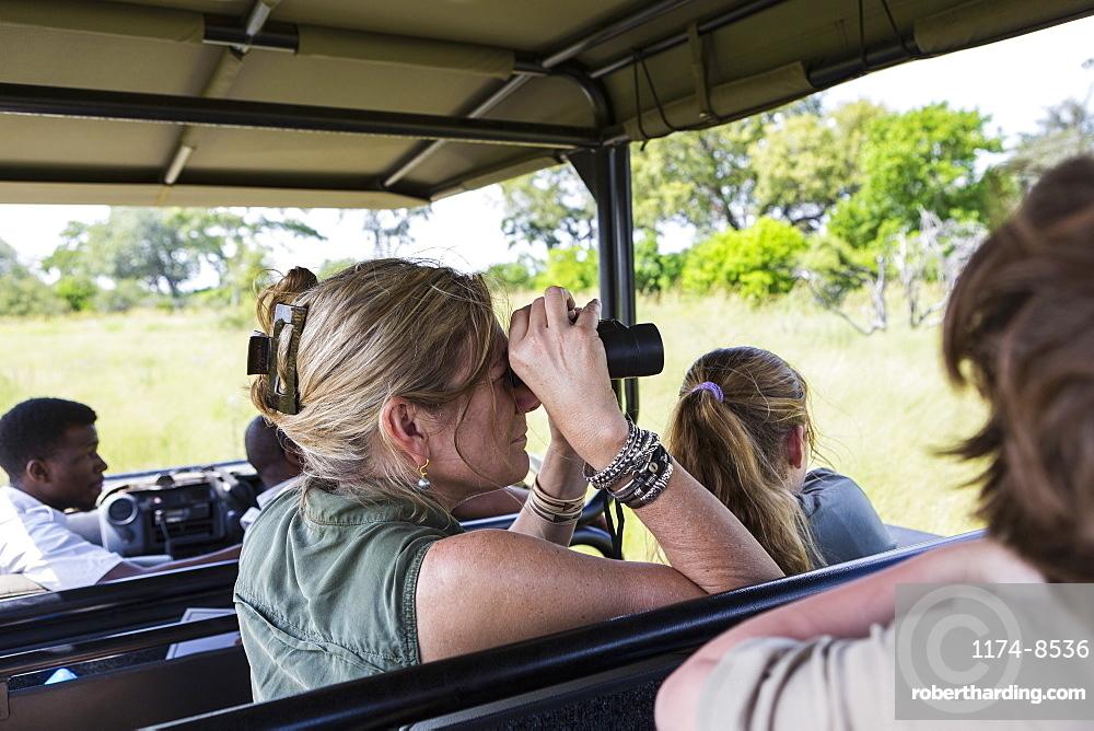 adult woman using binoculars in safari vehicle, Botswana