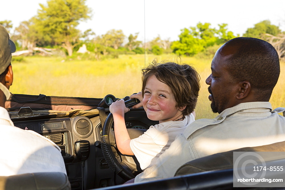 smiling Six year old boy steering safari vehicle, Botswana
