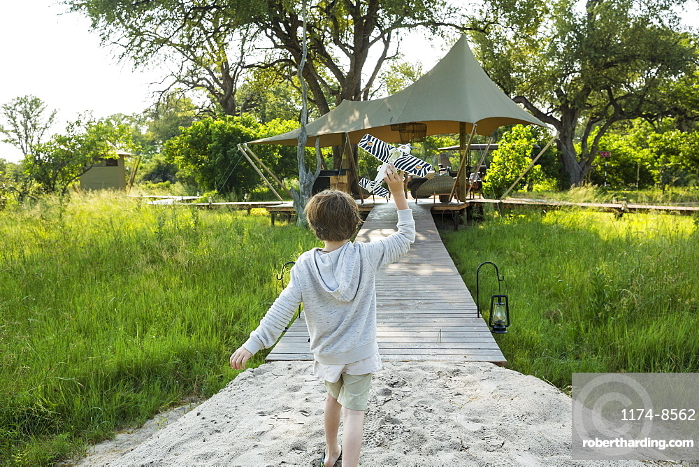 Six year old boy playing with toy airplane, tented camp, Botswana