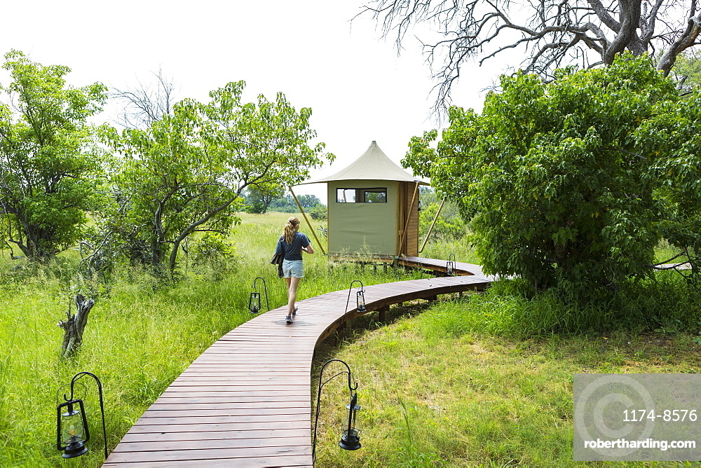 Thirteen year old girl walking wooden path, tented camp, Botswana