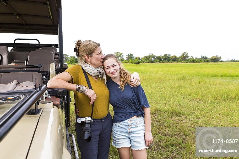 mother photographing with teen daughter near safari vehicle, Botswana