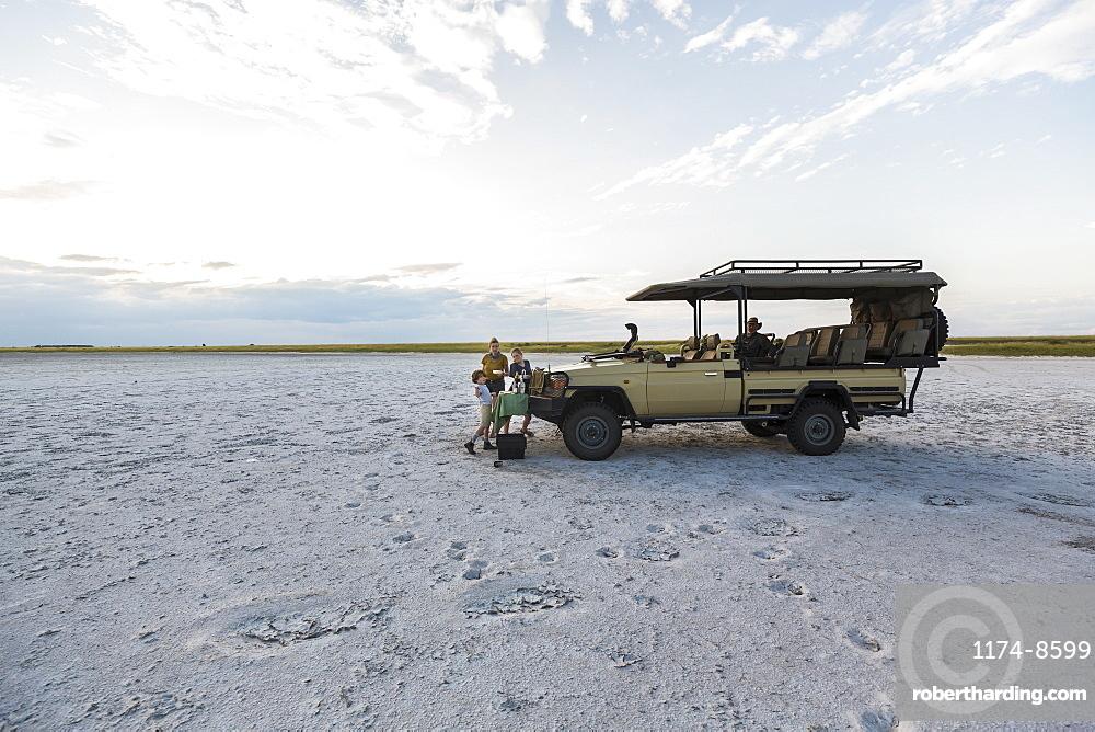 A safari vehicle parked in the salt pans landscape at dusk, Makgadikgadi Pan National Park, Botswana