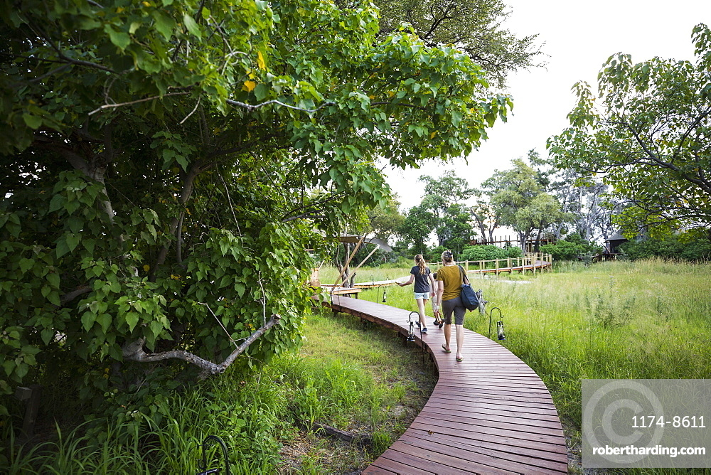 Two people, mother and teenage daughter walking on wooden path at a tented safari camp, Botswana