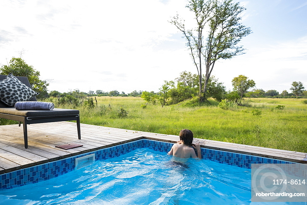 A boy in a swimming pool looking out at the landscape around a safari camp, Botswana