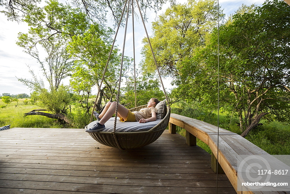 Thirteen year old girl resting in large swing on a deck at a safari camp, Botswana