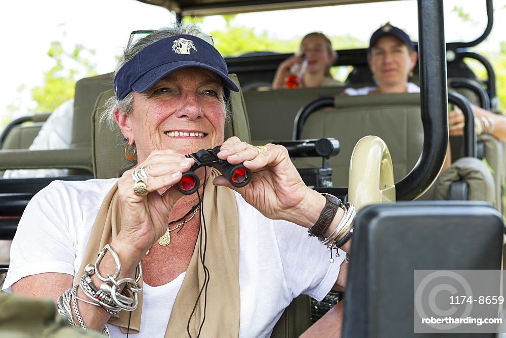 A family in a safari jeep in a wildlife reserve, a senior woman with binoculars, Okavango Delta, Botswana