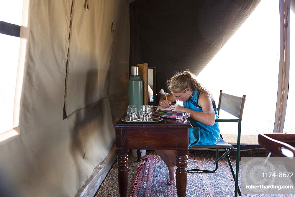 A twelve year old girl seated at a desk in a tent at a wildlife reserve camp, drawing, Okavango Delta, Botswana