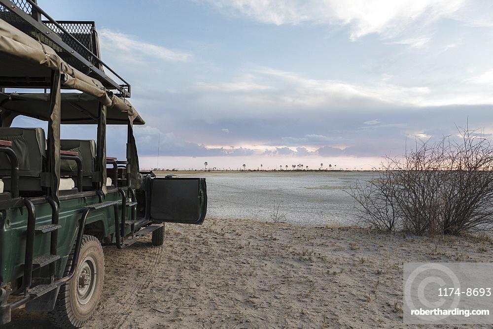 Safari vehicle with a view over the salt pan landscape, Kalahari desert