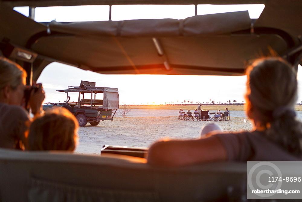 Family in safari vehicle taking photographs of a safari picnic at sunset
