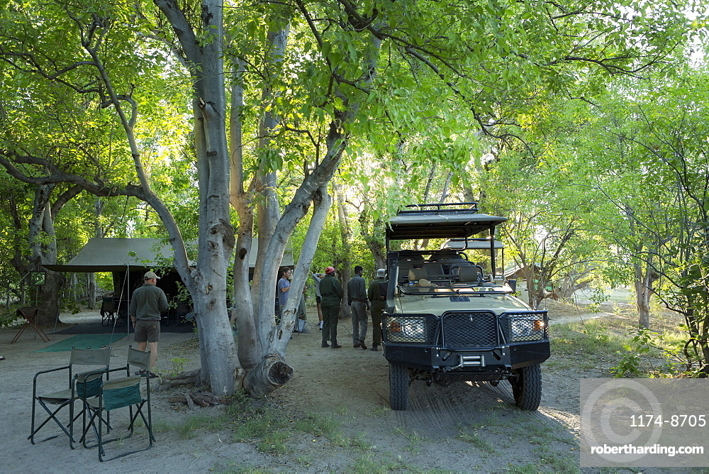 Safari vehicles and guides under the trees in a wildlife reserve camp, Okavango Delta, Botswana