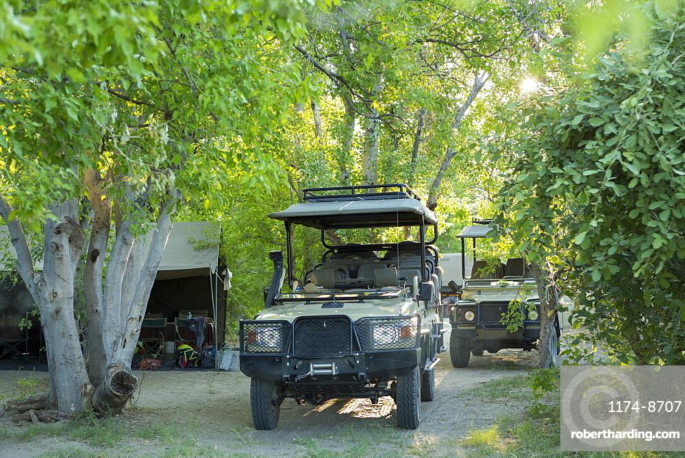 Safari vehicles under the trees in a wildlife reserve camp, Okavango Delta, Botswana