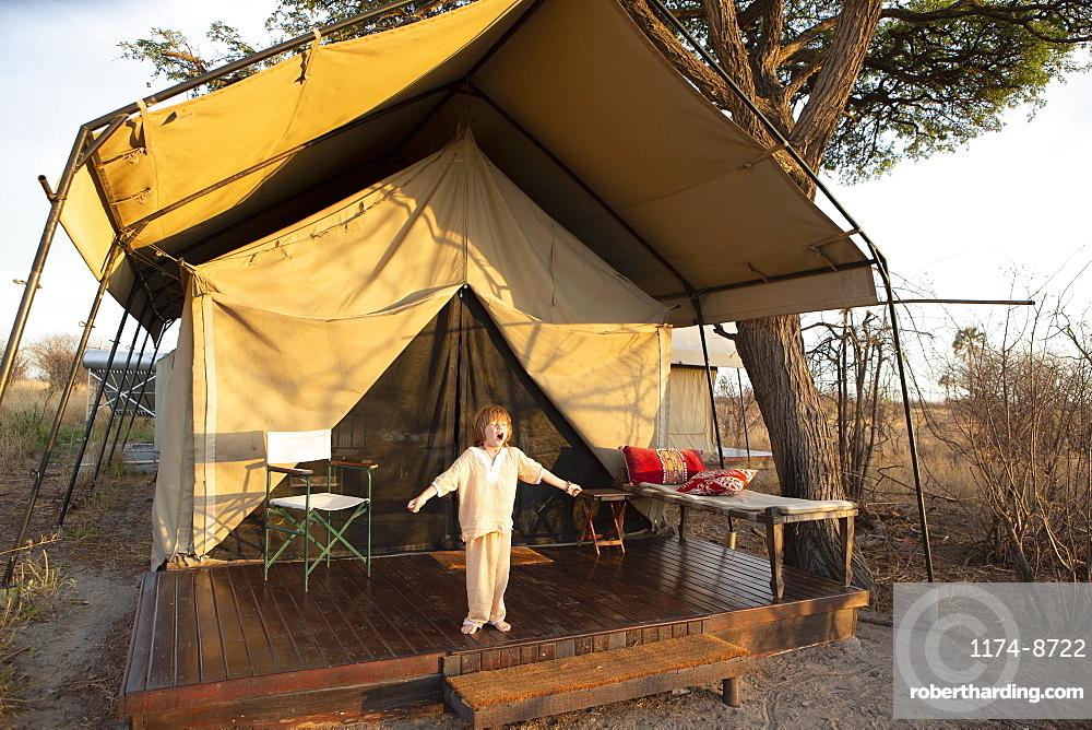A five year old boy standing outside a tent arms outstretched, yawning yawning outside tent, Kalahari Desert, Makgadikgadi Salt Pans, Botswana