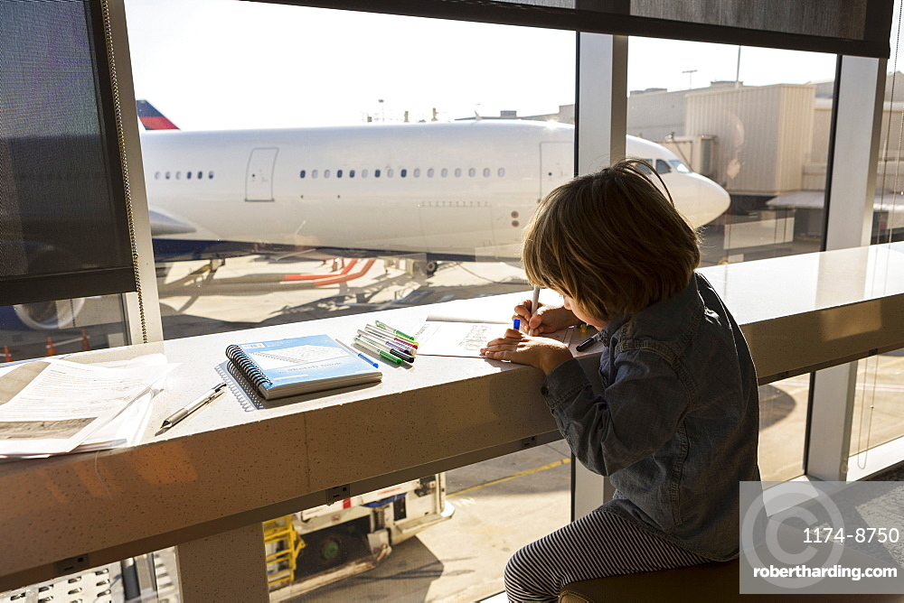 A five year old boy drawing, seated in airport lounge by a window