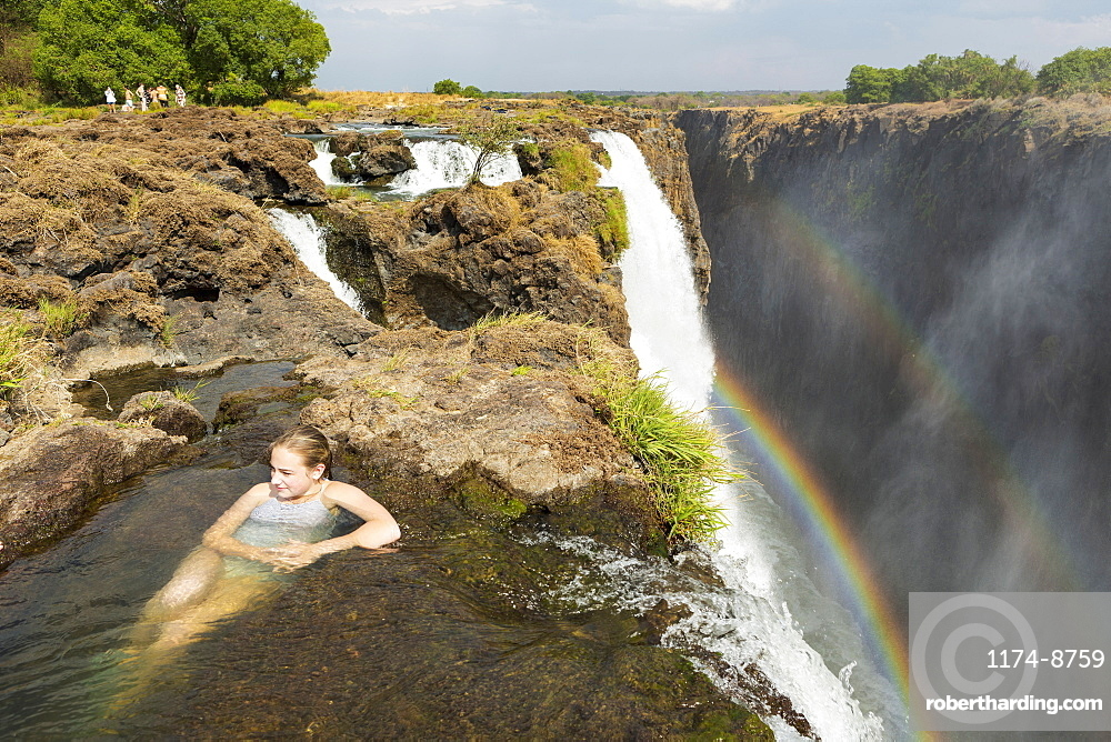 Young teenage girl in the water at the Devils Pool, on the cliff top overlooking Victoria Falls, Zambia, view from above