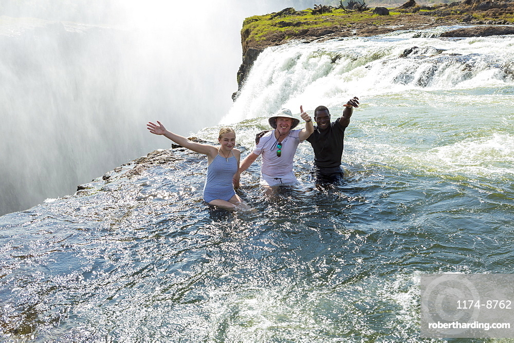 Three people, two men and young teenager standing in the waters of the Devil's Pool on the edge of the Victoria Falls, arms outstretched, Zambia