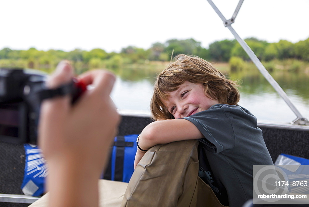 A five year old boy smiling at the camera on a river boat on the Zambezi River, Botswana
