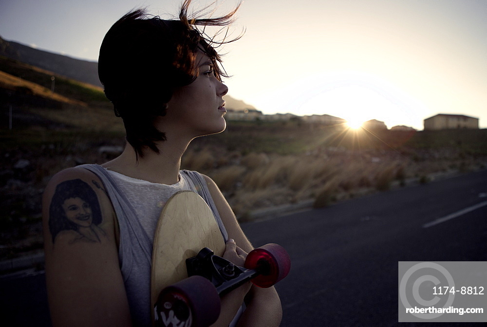 A young woman standing holding a skateboard