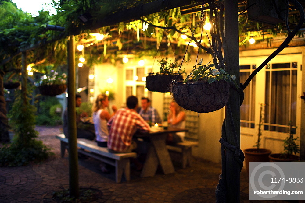 Group of people sitting outdoors at a table, hanging baskets in foreground, evening
