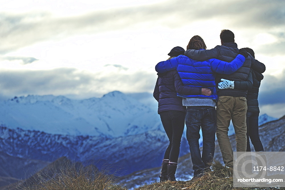 Rear view of four people standing arm in arm on a mountain, snow-capped peaks in the distance