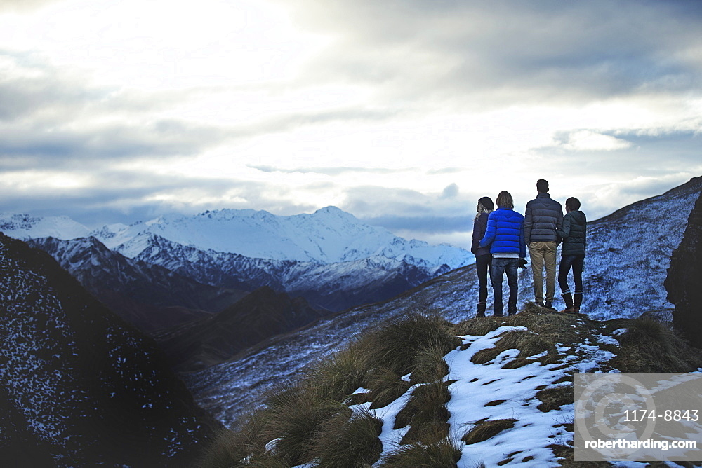 Rear view of four people standing side by side on a mountain, snow-capped peaks in the distance