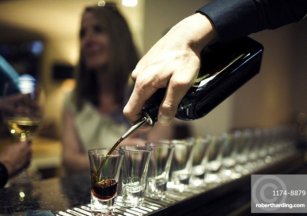 Close up of bartender pouring drinks from bottle into a row of shot glasses standing on bar counter, woman sitting in background