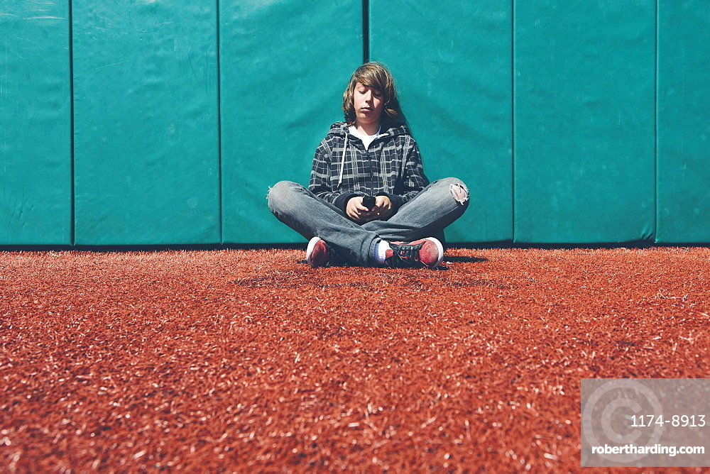 Teenage boy sitting against padded wall at sports field holding mobile phone