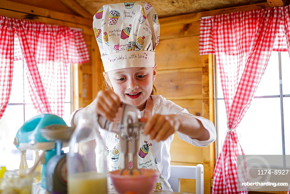 Young girl in wendy house using plastic whisk pretending to cook in kitchen