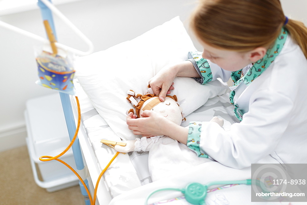 Young girl dressed as doctor putting plaster on doll's head in make-believe hospital bed