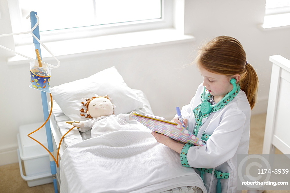 Young girl dressed as doctor writing notes next to pretend patient in make-believe hospital bed
