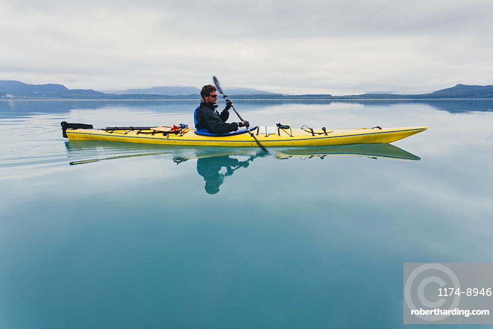Man sea kayaking inan inlet on the, Alaska coastline