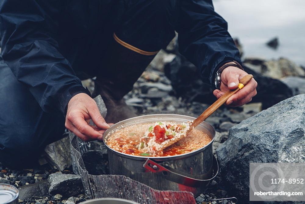 A wild camper stirring hot food in a pot cooking over a fire
