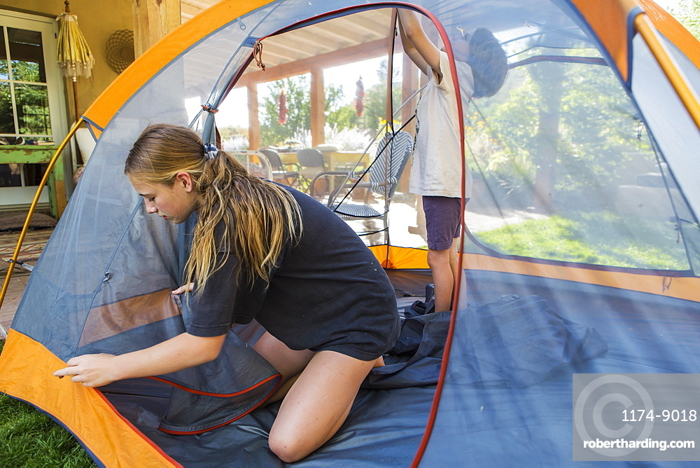 Teenage girl and her younger brother setting up tent to sleep out during a staycation, New Mexico, United States