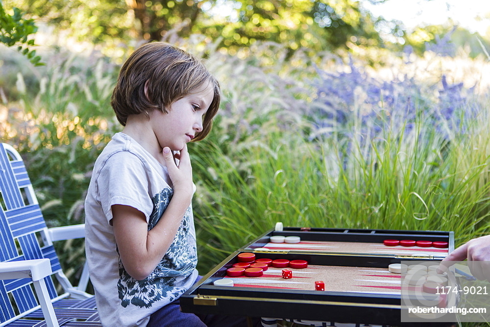 A young boy playing backgammon outdoors in a garden, New Mexico, United States